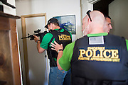 21 SEPTEMBER 2010 - PHOENIX, AZ: Phoenix Detective Mark Rao (CQ LEFT WITH RIFLE) covers a hallway while officers secure a home in central Phoenix Tuesday. They arrested three of the four people in the home on drugs and weapons charges. Crime has steadily dropped in Phoenix over the past few years, in line with national trends. The latest number released this month showed Phoenix reported fewer 2010 homicides, rapes, robberies, thefts - in addition to other major crimes -- compared with the same time period the previous year. Detectives in the Phoenix police department's Major Offender Unit make several arrests every day.   PHOTO BY JACK KURTZ