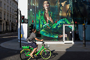 With a further 184 reported UK Covid deaths in the last 24 hrs, a total now of 43,414, a cyclist riding a Lime.E rental bike pedals beneath a billboard during the construction of a new Versace store on New Bond Street during the Covid pandemnic lockdown, now easing after three months of the Stay At Home policy but now being relaxed as the shops re-open, on 26th June 2020, in London, England. Government restrictions on the 2 metre rule is to be realxed on 4th July and replaced with 'one metre plus' in the hope it stimulates the struggling UK economy.