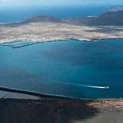 Caleta de Sebo on La Graciosa island is seen from the Mirador del Rio. In the foreground are the salt plants, Salinas del Rio.