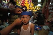 A boy is dressed up in princely clothes in remembrance of the Buddha at Poy Sang Long, the yearly ordination of novice monks, Mae Hong Son, Thailand. April 2003. His traditional headress contains female hair and fresh flowers.