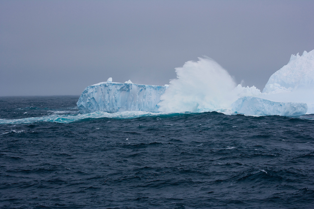 February 6th 2007. Southern Ocean. Waves crash over an iceberg floating in a storm in the Ross Sea off of Antarctica.