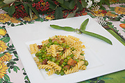 fusilli pasta with peas and safron sauce on white dish and table cloth with flowers and pods garnish, italian modern food,side view from above