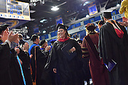 A graduate walks through a line of faculty on her way out of the Friday evening ceremony.
