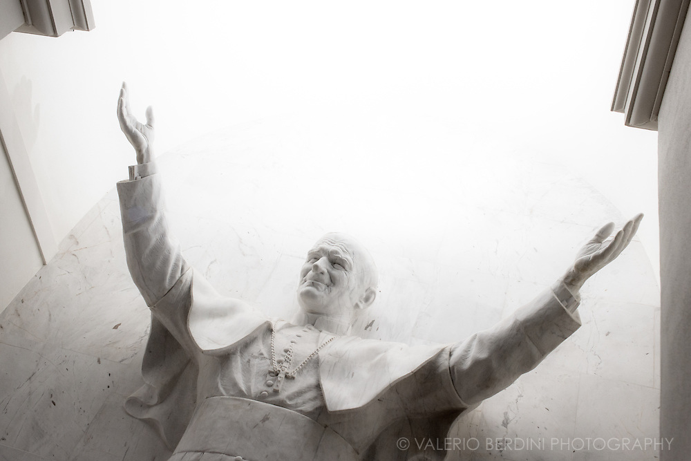 A statue of Pope Saint John Paul II, emerging from the stone, in the Church of the Holy Cross.