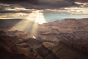 Sunlight breaks through the clouds and shines down onto the Colorado River. Viewed from Navajo Point on the East Rim Drive in Grand Canyon National Park.