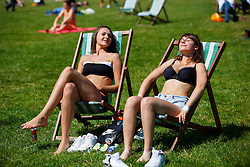 © Licensed to London News Pictures. 19/07/2016. London, UK. Karolina Swiszcz and Kasia Kusiak sunbathe as they enjoy the hottest day of the year so far in the UK in Green Park in London on Tuesday, 19 July 2016. Photo credit: Tolga Akmen/LNP