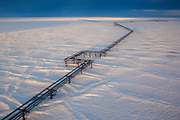 An elevated pipeline running above ground and the frozen tundra from Endicott oil production facility to the Alyaska 1 pipeline in Prudhoe