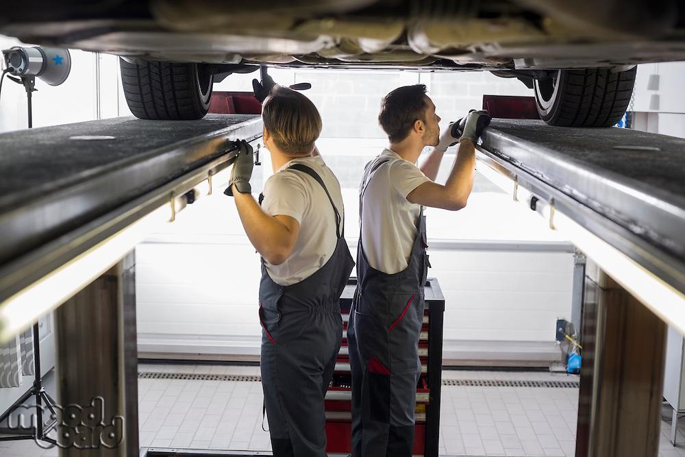 Side view of maintenance engineers examining car in repair shop