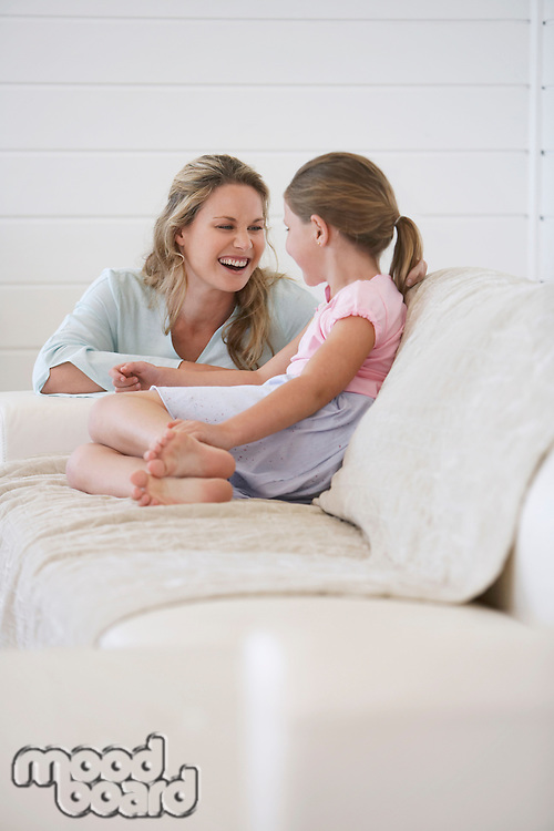 Mother crouching next to girl sitting on sofa