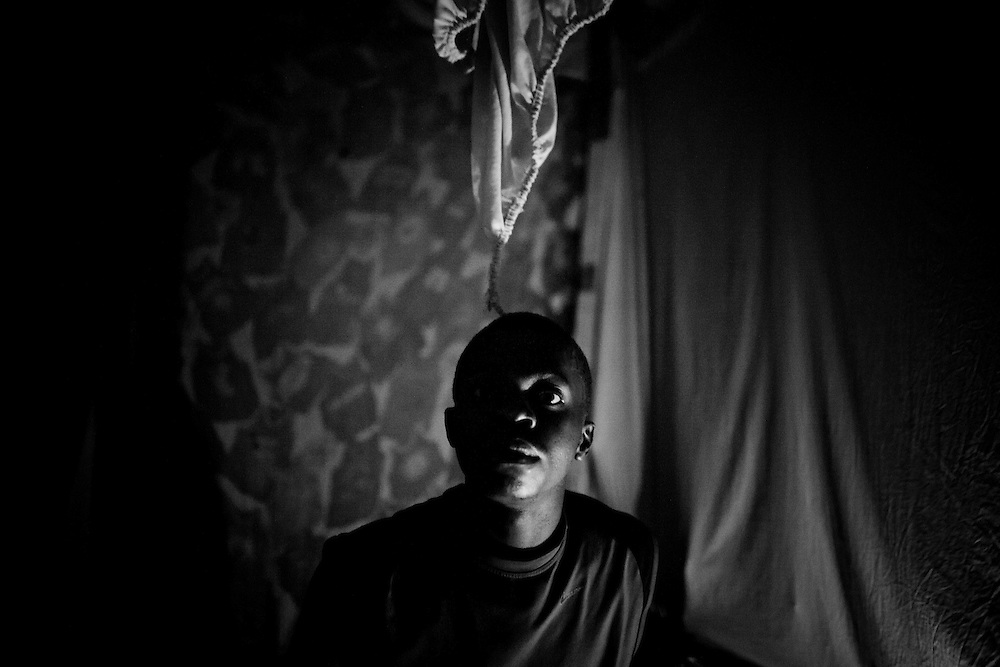 A man poses for a photo in his candle-lit tent a camp for those displaced by the recent earthquake in Petionville, outside Port-au-Prince, Haiti.