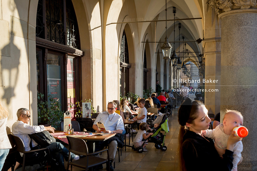 A mother feeds her baby beneath the arched passageway of the Renaissance Cloth Hall on Rynek Glowny market square, on 22nd September 2019, in Krakow, Malopolska, Poland.