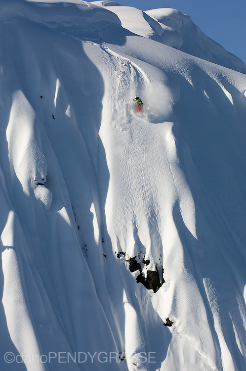 professional snowboarder Mad Jonsson drops into an extremely steep face near Terrace, British Columbia, Canada.