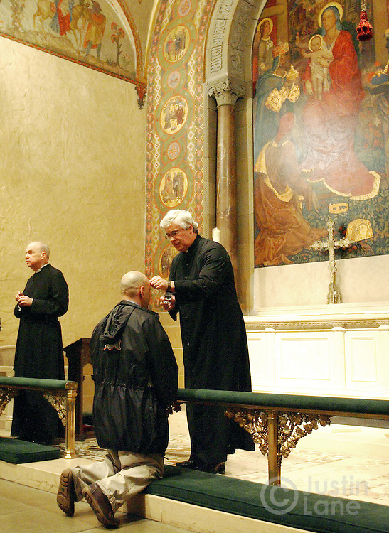 Rev. Kevin Bean (R) applies ashes to a man's forehead during observation of Ash Wednesday at St. Bartholomew's Church in New York, New York on Wednesday, Feb. 21, 2007. Ash Wednesday marks the beginning of Lent when many observant Catholics fast in preparation for the upcoming Easter festival. At left is Rev. Bruce Forbes.