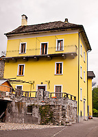 Ticino, Southern Switzerland. Moghegno. A local style house painted a cheerful yellow.