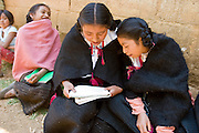 "26 APRIL 2005 - SAN CRISTOBAL DE LAS CASAS, CHIAPAS, MEXICO: Girls read the bible in Mayan before a Catholic mass in the Chumalan Indian community of Bautista Chico near San Cristobal de las Casas, Chiapas, Mexico. The Catholic Church in the Chiapas highlands is facing a threat from evangelical Protestant churches, which are experiencing explosive growth, and from ""traditionalist"" Catholic churches, which are not affiliated with the San Cristobal diocese and are controlled by local politicians and powerful indigenous leaders affiliated with the politicians. The traditionalists burn down churches and chapels affiliated with the diocese, threaten the priests and put indigenous men who worship with the diocese in jail.  PHOTO BY JACK KURTZ"