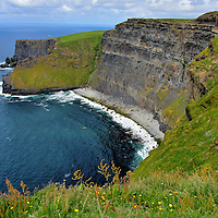 Concave Northern Scarp at Cliffs of Moher near Liscannor, Ireland<br /> Most tourists favor the walk along the southern cliff line and often miss this dramatic concave scarp along the northern edge.  This is one of my favorite views. To gain a perspective of its grand size, notice the sightseers walking along the trail in the upper right corner.