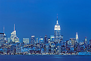 Panoramic skyline view of New York City, Manhattan at night, featuring, from left, One Bryant Park, the Empire State Building and the Chrysler Building, as seen from across the Hudson River.