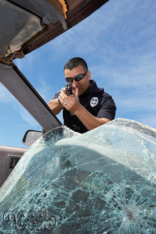 Police officer aiming gun through broken car windshield
