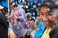 A boy squirts foam at passers by during carnival celebrations in La Paz, Bolivia