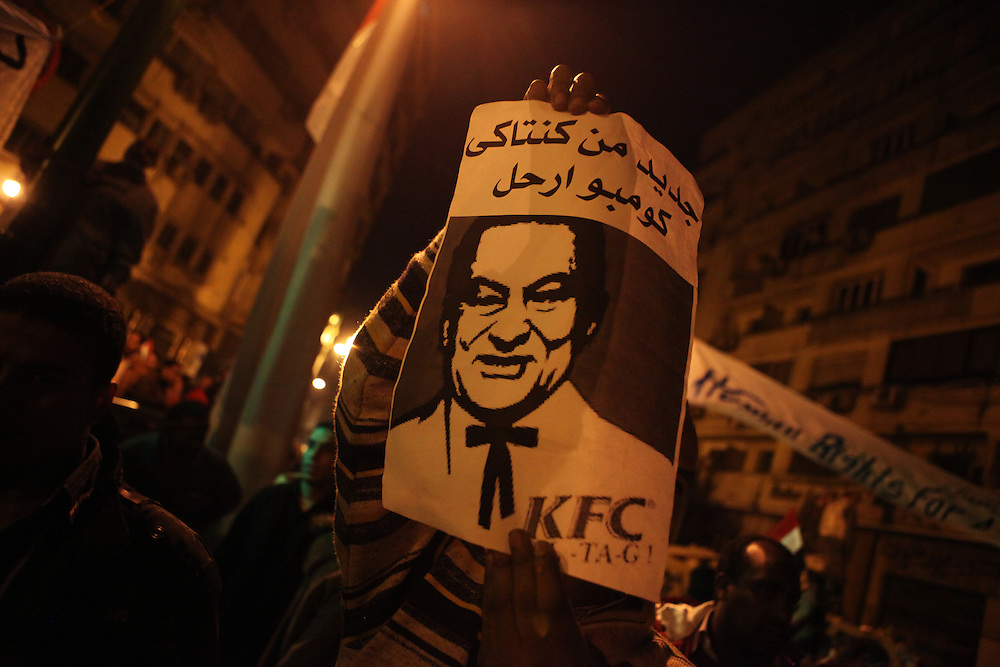 """A protester carries a sign reading, """"New from Kentucky, Combo Leave."""" It's a play on Mubarak propaganda which said that protesters were living well at Tahrir and being fed free KFC."""