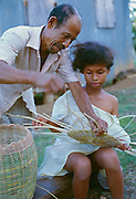 356203-1066 ~ Copyright:  George H. H. Huey ~ A Carib Indian girl, with her father, weaving a basket cover, Village of Salibia, Carib Territory [east coast].  Dominica.  Caribbean.