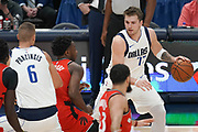 Dallas Mavericks guard Luka Doncic (77) draws a crowd of Toronto Raptors forward OG Anunoby (3), Pascal Siakam (43) and Fred VanVleet (23) while Dallas Mavericks forward Kristaps Porzingis (6) provides a screen during an NBA basketball game, Saturday, Nov. 16, 2019, in Dallas. The Mavericks defeated the Raptors 110-102. (Wayne Gooden/Image of Sport)