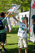 Renato Quiros, 9, of Costa Rica proudly holds up his hand-made sign in the Ironman Village in City Park on Thursday to support his father, Romulo, an Ironman hopeful competing in Sunday's Ford Ironman triathlon...