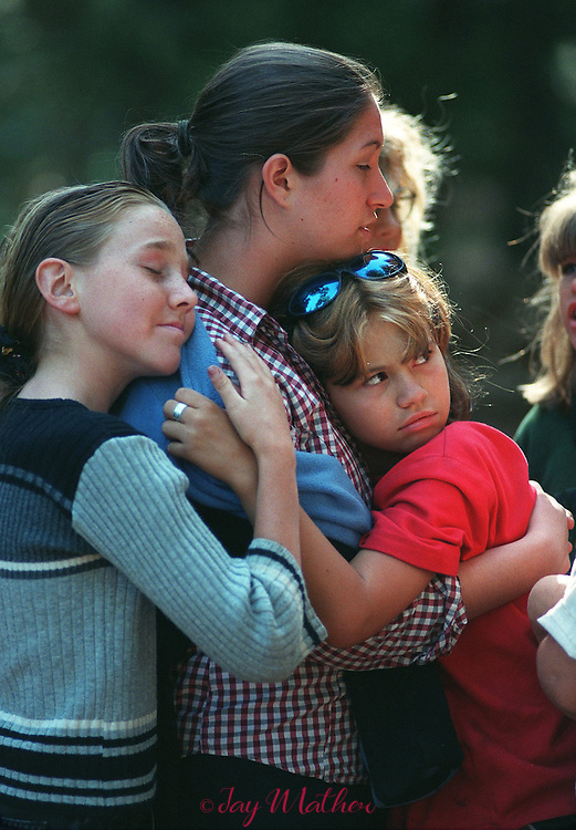 Saying goodbye to a favorite counselor during the last afternoon of an eight-day stay at Camp Menzies Girl Scout Camp is a touching moment for Alyssa Bedford (cq), left and Bobbie Jo Alexander, right.  The counselor of their affection is  Lisa Cooper (cq).  July 2, 2000.