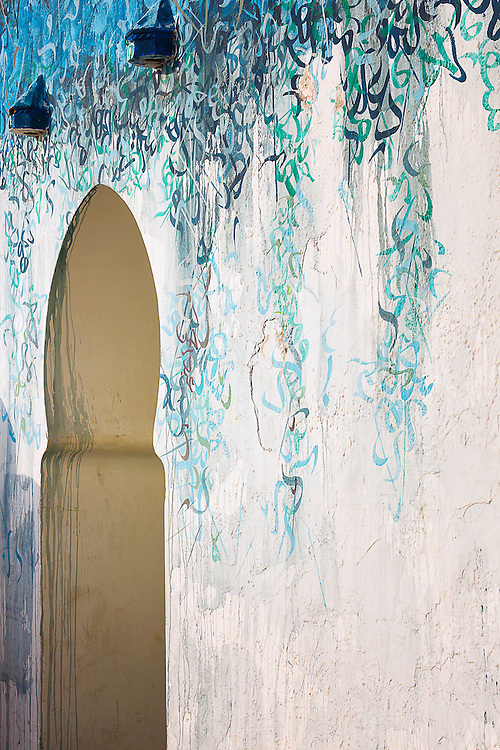 Artistic calligraphy painting on a house wall in Assilah, Morocco.