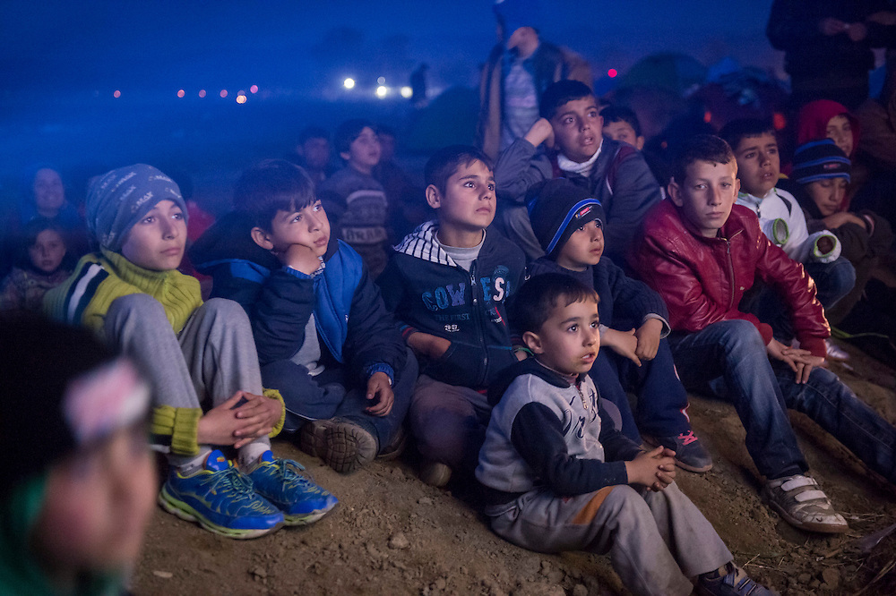 March 5, 2016 - Idomeni, Greece:  children watch a movie in the  open air in the make shift refugee camp at the  Idomeni border crossing in Greece. 13,000 refugees are stuck here after Macedonia closed the border. New arrivals come in every day, making living conditions more and more difficult. (Steven Wassenaar/Polaris)