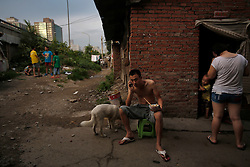 A picture made available on 30 July 2013 of Chinese residents living in a slum or shanty town area by the second ring road of Beijing, metres away from the prosperous Central Business District (CBD), separated only by a busy highway in China, 29 July 2013. Beijing announced plans to spend 500 billion yuan (61.5 billion euros) to renovate shanty towns within the fourth ring road according to local media. The five-year plan is expected to affect more than 230,000 households. China's massive urbanization push has resulted in the creation of large pockets of shanty towns and slums in urban areas as millions of migrant workers shifting to the cities are often priced out of city-centre properties. Slum or shanty town dwellers often live in dirty and cramped conditions, where they have no running water in their homes and have to share toilet and shower facilities.