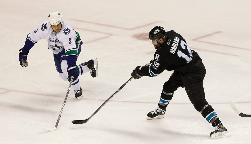 May 22, 2011; San Jose, CA, USA; San Jose Sharks center Patrick Marleau (12) shoots the puck in front of Vancouver Canucks defenseman Kevin Bieksa (3) during the first period of game four of the western conference finals of the 2011 Stanley Cup playoffs at HP Pavilion. Mandatory Credit: Jason O. Watson / US PRESSWIRE
