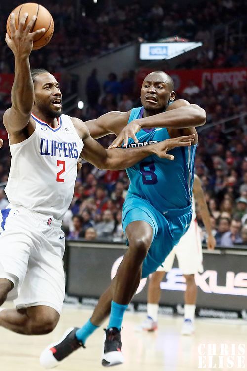 LOS ANGELES, CA - OCT 28: Kawhi Leonard (2) of the LA Clippers drives past Bismack Biyombo (8) of the Charlotte Hornets during a game on October 28, 2019 at the Staples Center, in Los Angeles, California.