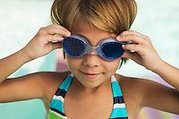 Girl (7-9) adjusting goggles smiling.