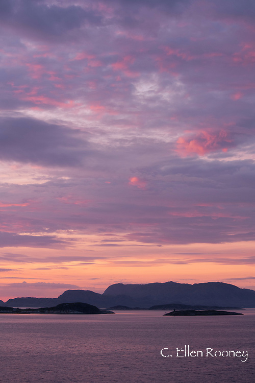 Sunset over rocky islands near Helgelandskysten on the northwest coast of Norway from a Hurtigruten ship. Norway, Europe
