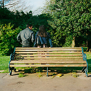 An Asian couple standing in front of a park bench in the East End