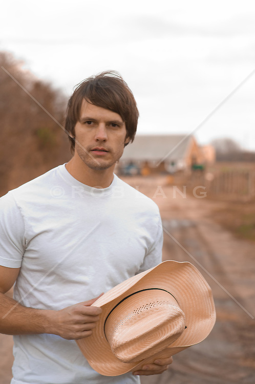 Young man on a dirt road holding his cowboy hat