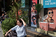 A lady rests into the sun outside the window of the Sunglass Hut retailer in Covent Garden whose current slogan is 'Face the Sun', on 15th June 2019, in London, England.