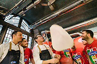 "NAPLES, ITALY - 8 DECEMBER 2017: Gino Sorbillo (39, center), a Master Pizzaiuolo (pizza chef) and owner of Pizzeria Gino Sorbillo, performs in front of his co-workers as he twirls a pizza dough in the air, here in his pizzeria in Naples, Italy, on December 8th 2017. According to Gino Sorbillo, twirling pizza in the air is a performance practiced by older generations of pizziauolis that doesn't benefit the pizza making.<br /> <br /> On Thursday December 7th 2017, UNESCO added the art of Neapolitan ""Pizzaiuolo"" to its list of Intangible Cultural Heritage of Humanity.<br /> <br /> The art of the Neapolitan 'Pizzaiuolo' is a culinary practice comprising four different phases relating to the preparation of the dough and its baking in a wood-fired oven, involving a rotatory movement by the baker. The element originates in Naples, the capital of the Campania Region, where about 3,000 Pizzaiuoli now live and perform. Pizzaiuoli are a living link for the communities concerned. There are three primary categories of bearers – the Master Pizzaiuolo, the Pizzaiuolo and the baker – as well as the families in Naples who reproduce the art in their own homes. The element fosters social gatherings and intergenerational exchange, and assumes a character of the spectacular, with the Pizzaiuolo at the centre of their 'bottega' sharing their art.<br /> <br /> In Naples, pizza makers celebrated the victory by giving away free pizzas."