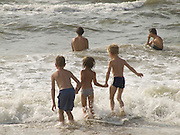 three children having fun in the waves