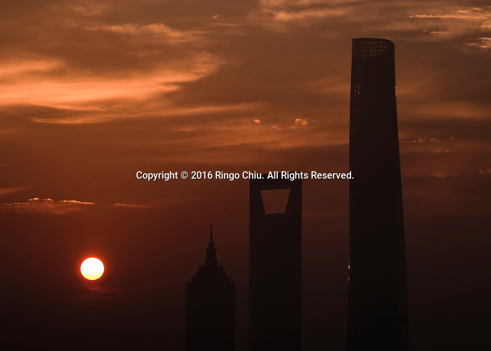 View of the Pudong skyline as seen at sunrise from the Meridien Hotel in Shanghai, China, Shanghai is the most populous city in China and the most populous city proper in the world. It is one of the four direct-controlled municipalities of China, with a population of more than 24 million as of 2014. It is a global financial centre, and a transport hub with the world's busiest container port. Located in the Yangtze River Delta in East China, Shanghai sits on the south edge of the mouth of the Yangtze in the middle portion of the Chinese coast. The municipality borders the provinces of Jiangsu and Zhejiang to the north, south and west, and is bounded to the east by the East China Sea. A major administrative, shipping, and trading town, Shanghai grew in importance in the 19th century due to trade and recognition of its favourable port location and economic potential. The city was one of five forced open to foreign trade following the British victory over China in the First Opium War while the subsequent 1842 Treaty of Nanking and 1844 Treaty of Whampoa allowed the establishment of the Shanghai International Settlement and the French Concession. The city then flourished as a center of commerce between China and other parts of the world (predominantly Western countries), and became the primary financial hub of the Asia-Pacific region in the 1930s. However, with the Communist Party takeover of the mainland in 1949, trade was limited to socialist countries, and the city's global influence declined. In the 1990s, the economic reforms introduced by Deng Xiaoping resulted in an intense re-development of the city, aiding the return of finance and foreign investment to the city. Shanghai has been described as the &quot;showpiece&quot; of the booming economy of mainland China; renowned for its Lujiazui skyline, museums and historic buildings, such as those along The Bund, the City God Temple and the Yu Garden.(Photo by Ringo Chiu/PHOTOFORMULA.com)<br /> <br /> Usage Notes: This 