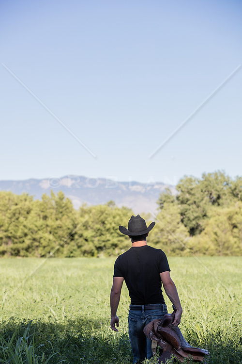 cowboy walking through a field with a saddle