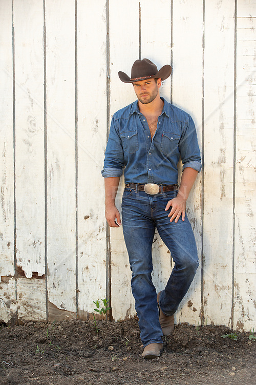 very good looking cowboy leaning against a rustic white barn