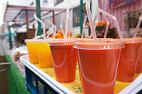 Close-up of fruit juices on display at market stall