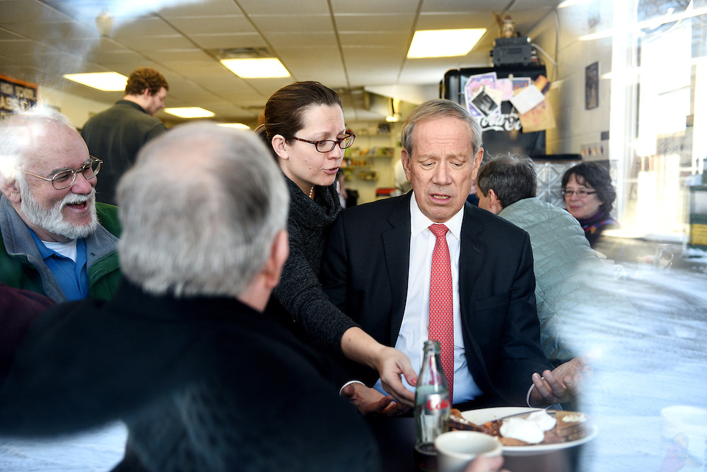 Lebanon Diner owner Karen Liot Hill moves former New York Governor George Pataki's breakfast plate to another table to encourage him to speak with more guests as Dan Nash, of Lebanon, looks on at left, during an event at the restaurant in Lebanon, N.H. Monday, Feb. 2, 2015. Pataki is visiting voters in the region and considering a run for the presidency. (Valley News - James M. Patterson)<br /> Copyright &copy; Valley News. May not be reprinted or used online without permission. Send requests to permission@vnews.com.