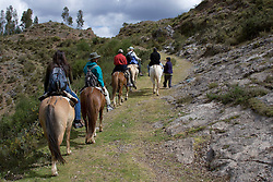 Tourists horseback riding to Temple of the Moon, Cuzco, Peru, South America