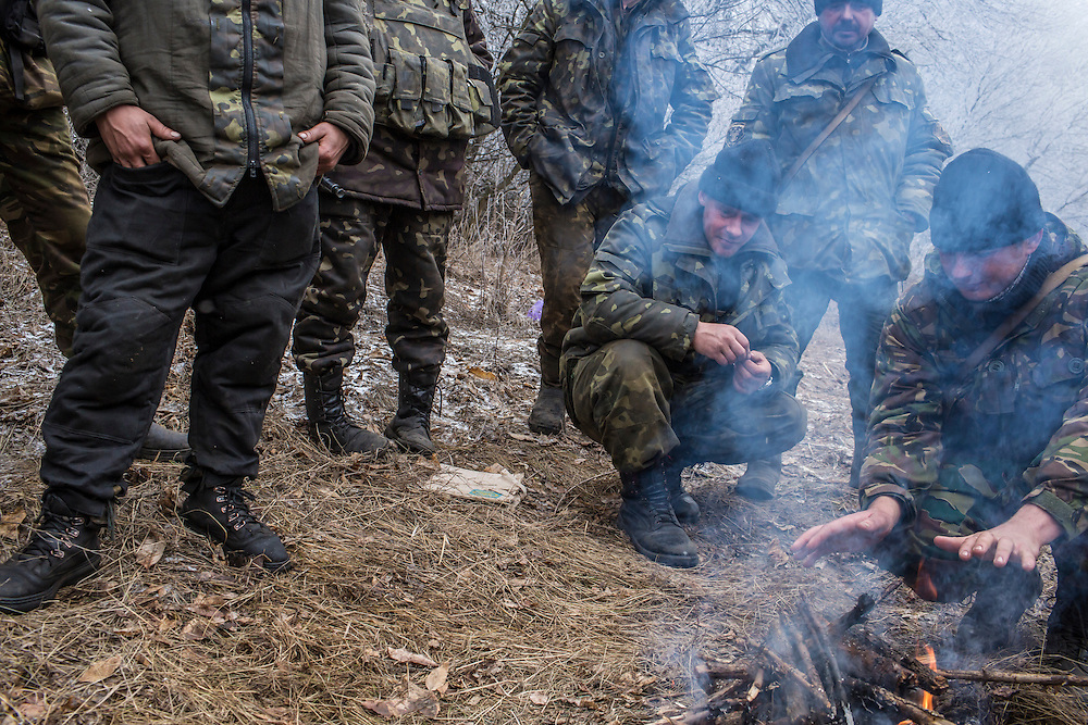 ARTEMIVSK, UKRAINE - FEBRUARY 15: Ukrainian soldiers stand around a fire along the road leading to the embattled town of Debaltseve on February 15, 2015 outside Artemivsk, Ukraine. A ceasefire scheduled to go into effect at midnight was reportedly observed along most of the front, save for near the embattled town of Debaltseve. (Photo by Brendan Hoffman/Getty Images) *** Local Caption ***