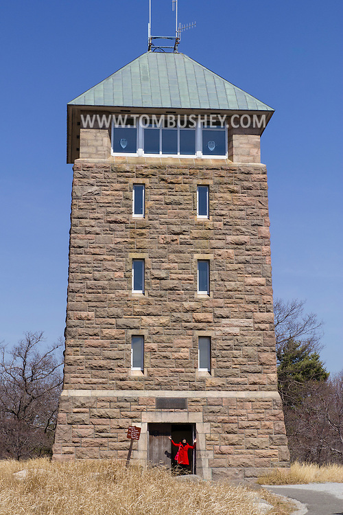 Bear Mountain, New York -A woman stands in the doorway of Perkins Memorial Tower at Bear Mountain State Park on April 13, 2015. The 40-foot tall stone lookout tower was built in 1931-34 and dedicated as the Perkins Memorial Tower to honor former Chairman of the Palisades Interstate Park Commission.
