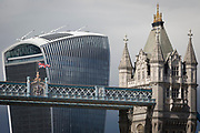 The British Union Jack flag flies from the high-level walkway of Victorian-era Tower Bridge, near the modern Walkie Talkie building (aka 20 Fenchurch Street), on 14th September 2017, in London, England.