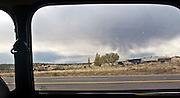 strange cloud, rural house, and arid landscape through a water spotted auto window and parallel power lines across the panorama image along US 550 in NW New Mexico, USA framed by the window of a classic Mini Cooper.